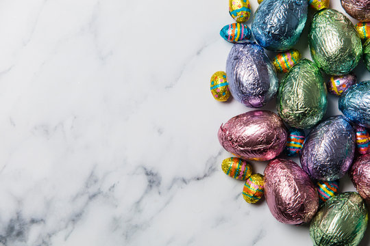 Easter egg chocolate treats wrapped in shiny coloured foil on  marble background