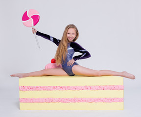 diet and weightloss concept - cute little girl gymnast with big slice of cake and lollipop over white