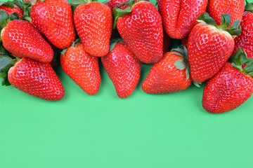 Ripe sweet strawberries on green background.