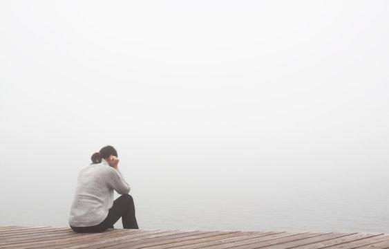 Junge Frau sitzt einsam am Rand eines Holzweges einer Brücke gebückt und traurig in Gedanken.