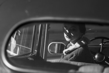 Woman dressed in old-fashioned style sits in a retro car together with her man