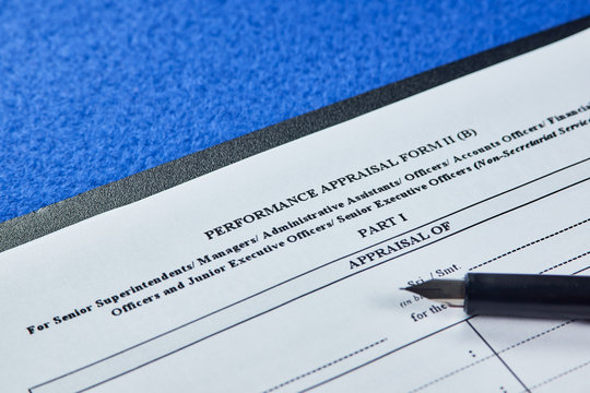Performance appraisal form next to black pen on blue velvet background. Close-up