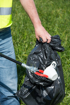 A man cleans a meadow from littering, a plastic bottle, for environmental protection in Uster, Zurich, Switzerland.