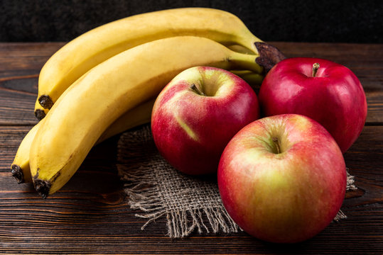 Banana and red apple on dark wooden background.
