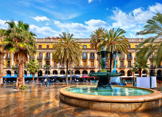 Royal area in Barcelona, Spain. Fountain with statues and high palm trees among traditional Spanish architecture at main central square of old town. Summer landscape with blue sky and clouds. Fototapete