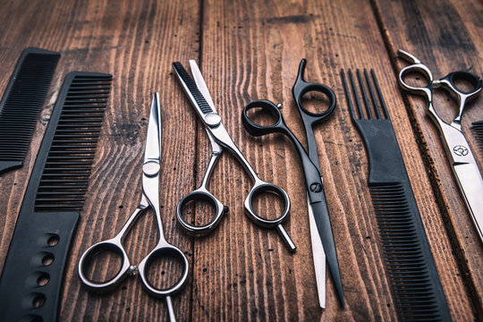 Stylish professional barber scissors on vintage wooden table, hairdresser salon concept, hairdressing tool set. Haircut accessories