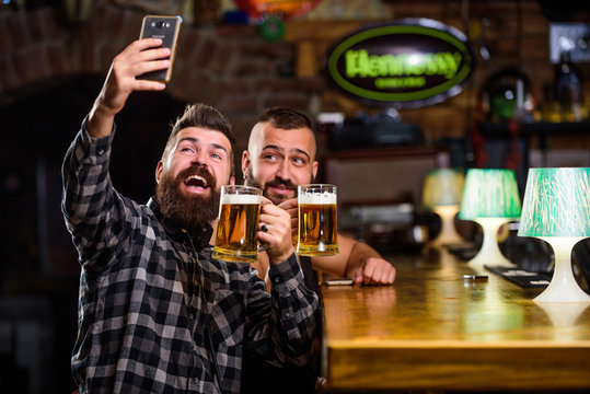 Man in bar drinking beer. Online communication. Man bearded hipster hold smartphone. Taking selfie concept. Take selfie photo to remember great evening in pub. Send selfie to friends social networks