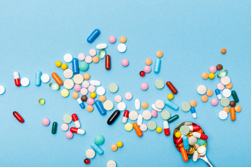 Top view of colorful pills and spoon on blue surface