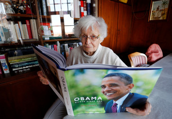 Lisel Heise, a 100-year-old former teacher, looks through a book with photographs of former U.S. President Barack Obama as she meets journalists in the living room of her house in Kirchheimbolanden