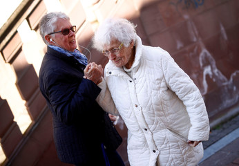Lisel Heise (R), a 100-year-old former teacher, greets a friend as she walks through Kirchheimbolanden