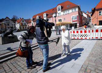 A TV crew films Lisel Heise, a 100-year-old former teacher, walking through Kirchheimbolanden
