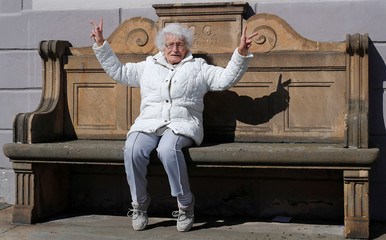 Lisel Heise, a 100-year-old former teacher, sits on a stone bench from 1921 and flashes victory signs in front of the townhall in Kirchheimbolanden