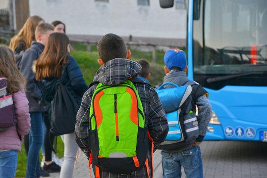 Schüler mit Schulrucksack der Grundschule auf dem morgendlichen Weg zum Schulbus