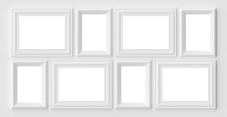 White photo or picture frames on the white wall with shadows