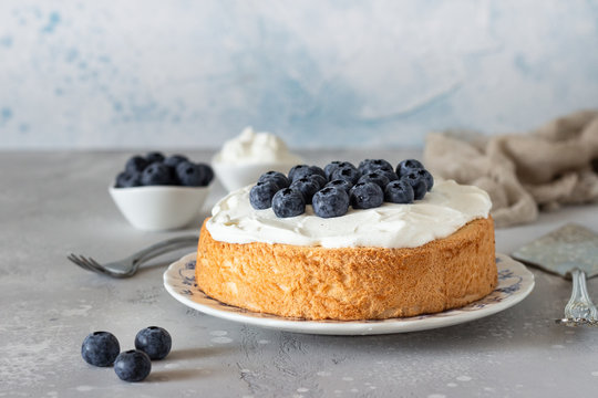 Angel food cake with whipped cream and fresh blueberries.