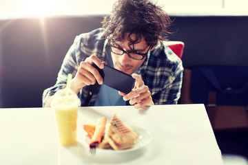 leisure, food, eating and people concept - man with smartphone photographing his lunch at cafe