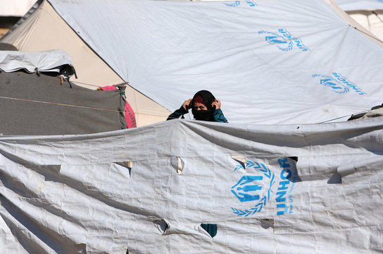 A woman stands outside a tent at al-Hol displacement camp in Hasaka governorate