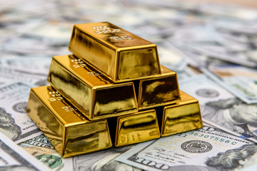 Gold bars with hundred dollar banknotes as background Fototapete