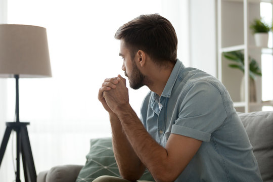 Thoughtful serious man sitting on sofa at home, lost in thoughts