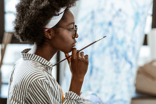 African-American artist feeling thoughtful working on new picture