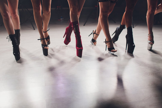 young striptease dancer moving in high heels shoes on stage in strip night club, Pole dancing.