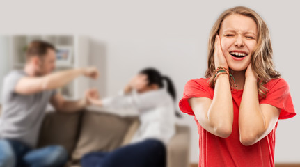 domestic violence, assault and social issue concept - unhappy stressed teenage girl covering her ears when her mother and father having fight background