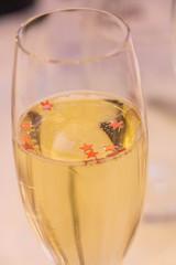 Flûte à champagne remplie de champagne avec des paillettes rouges en forme d'étoile