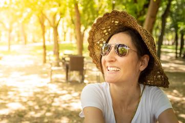 Happy brunette woman enjoying the summer in a recreation area