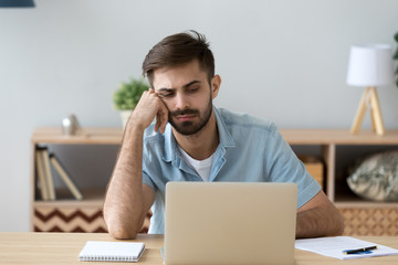 Tired student or employee working with laptop, doing boring job