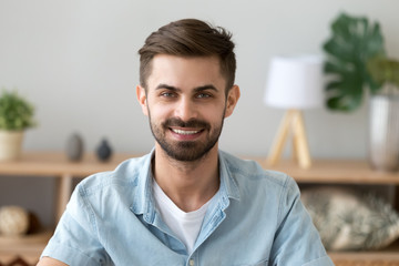 Head shot portrait of smiling satisfied man looking at camera