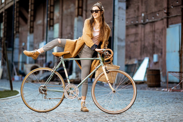 Full body portrait of a beautiful stylish woman dressed in coat standing with retro bicycle...