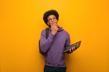 Young african american student man holding a calculator doubting and confused