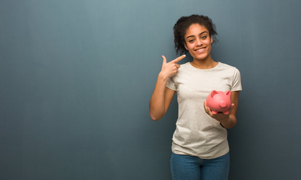 Young black woman smiles, pointing mouth. She is holding a piggy bank.