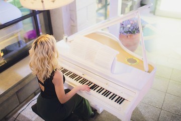 Beauty Blonde Woman Portrait. Beautiful bride with long curly blond hair sitting at the piano. White Hair. Perfect Skin and Make up. Hair Extensions.