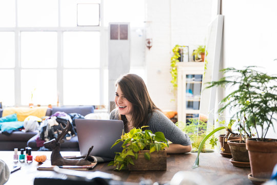 Transgender woman looking at her laptop at home