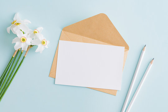 Mockup white wedding invitation and envelope with white daffodils on a blue background