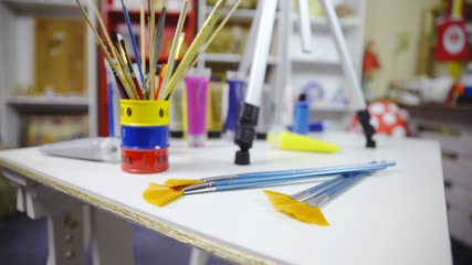 Artist brushes and color tubes on table