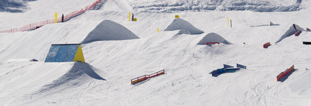 Snowpark with ski ramps, kickers, rails for big air jumping, jibbing, etc. of freestyle snowboarders and skiers