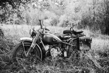 Fototapeta Old Tricar, Three-Wheeled Motorbike Of Wehrmacht, Armed Forces Of Germany Of World War II Time In Summer Forest. Photo In Black And White Colors