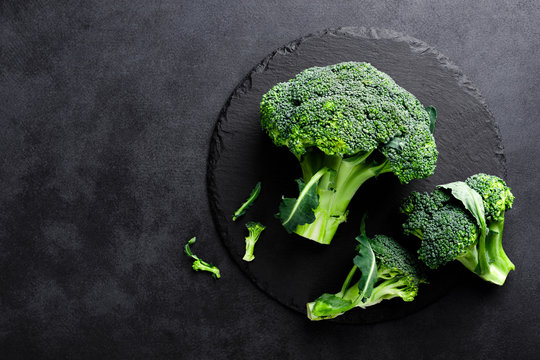 Fresh broccoli florets on black background, top view