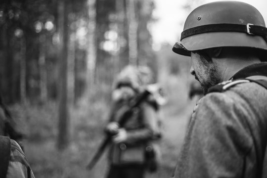 Re-enactors Dressed As World War II German Wehrmacht Soldiers Marching Walking Along Forest Road In Summer Day. Photo In Black And White Colors. Military German Soldier Of WWII Times