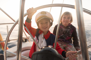Positive kids in captain hat floating on expensive boat on sea in sunny day