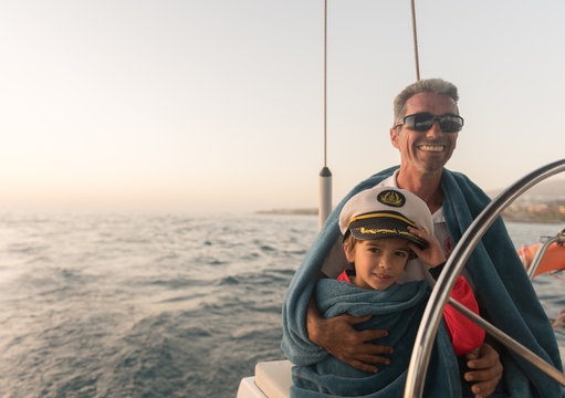 Positive father in sunglasses and towel embracing happy kid in captain hat and sitting on expensive boat floating on water