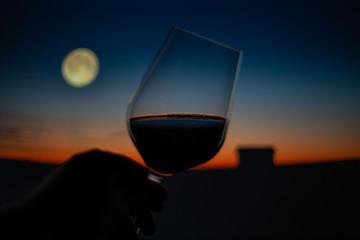Hand hält Weinglas vor romantischer Kulisse