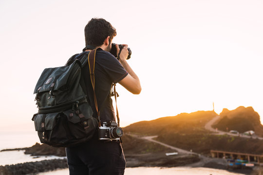 Back view of tourist with knapsack and retro camera standing on mountain Teide in evening on blurred background in Tenerife, Canary Islands, Spain