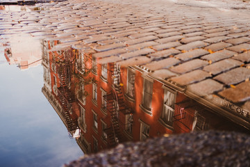 Reflection of old red building in water of puddle on cobblestone pavement of street, New York
