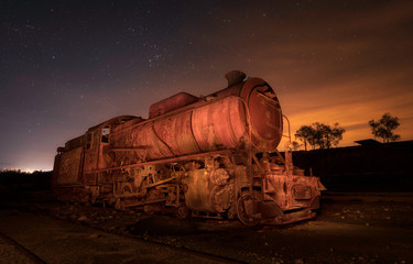Old deserted retro train on rails between field and heaven with stars in evening in Rio Tinto, Spain