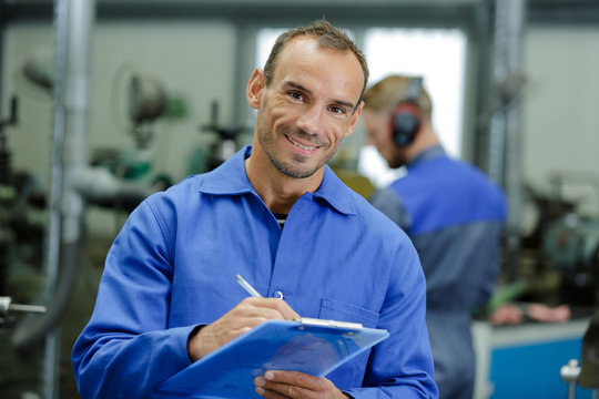 portrait of factory supervisor holding clipboard