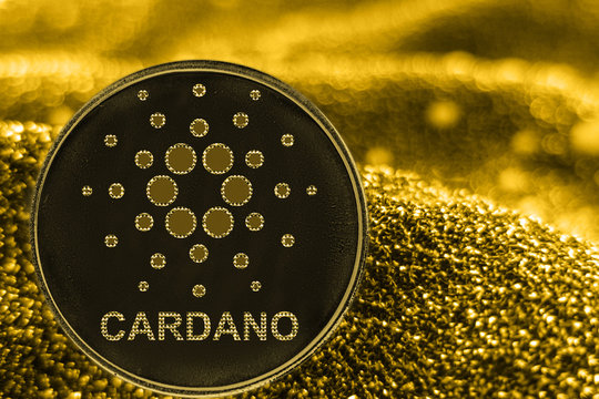 Coin cryptocurrency ADA Cardano on golden background.