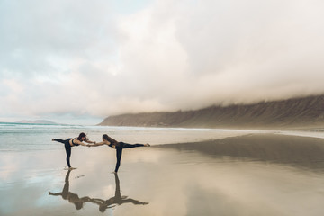Side view of two barefoot females in sportswear performing exercise on wet sand near sea on overcast day